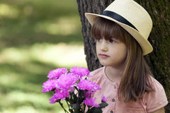 Little cute girl standing in a park and holding a bouquet and wa Stock Photo