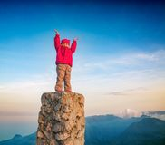 Little cute girl standing on a top above the mountain valley Royalty Free Stock Image