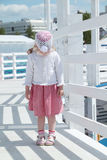 Little cute girl stands on white wooden bridge. And looks down Stock Photo