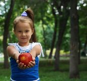 Little cute girl stretching apple. Little cute girl stretching red apple Royalty Free Stock Photos
