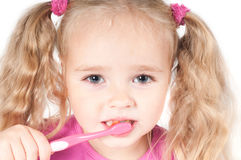 Little cute girl in studio brushing teeth Royalty Free Stock Photography