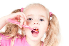 Little cute girl in studio brushing teeth Royalty Free Stock Image