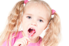 Little cute girl in studio brushing teeth Stock Photo