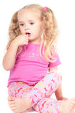 Little cute girl in studio eating candy Royalty Free Stock Image