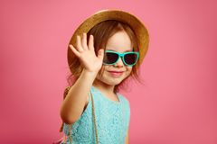 Little cute girl in summer hat and sunglasses waving at you,expressing joy and happiness, standing on pink isolated royalty free stock images