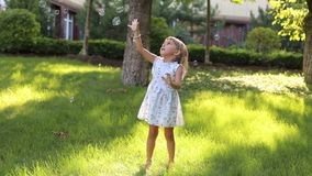 A little cute girl in a summer light dress playing with soap bubbles in the Park. On the green grass stock video