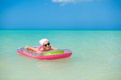 Little cute girl sunbathing on pink air-bed in Stock Image