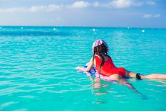 Little cute girl swimming on a surfboard in the Stock Images