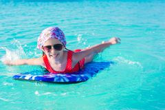 Little cute girl swimming on a surfboard in the Royalty Free Stock Photos