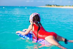 Little cute girl swimming on a surfboard in the Royalty Free Stock Image