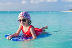 Little cute girl swimming on a surfboard in the Stock Photo