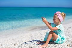 Little cute girl taking pictures on the phone at Stock Photo