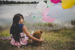 Little cute girl with teddy bear sitting on long green grass out