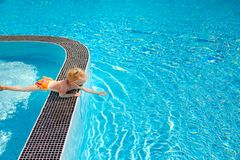 The little cute girl , touching the water in the swimming pool. royalty free stock photos