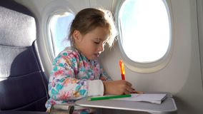 A little girl traveling by an airplane and drawing a picture with colorful pencils. A little cute girl traveling by an airplane and drawing a picture with