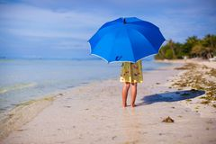Little cute girl with umbrella on exotic beach Royalty Free Stock Images