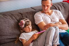 Little cute girl is using tablet, her father is playing console . stock photography