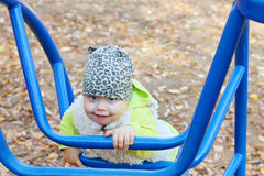 Little cute girl in vest climbs on blue ladder Royalty Free Stock Images