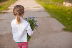 Little cute girl walking with a bouquet of flowers Royalty Free Stock Images