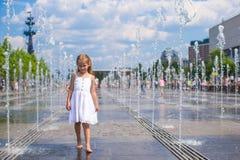 Little cute girl walking in open street fountain Royalty Free Stock Image