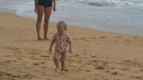 Little cute girl walking on sandy beach stock footage