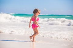 Little cute girl walking on the white sandy beach Royalty Free Stock Image
