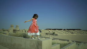 Little cute girl walks on the wall in big amphitheatre. Child have a dream. Kid jumps from fence. Pink dress flutters in stock footage