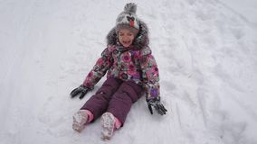 Little cute girl in warm clothes is sitting on the snow and crying. Small princess  walking outside in the winter  playi stock video footage