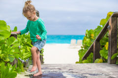 Little cute girl washes out the sand from her feet Royalty Free Stock Image