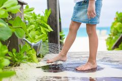 Little cute girl washes out the sand from her feet Royalty Free Stock Photography