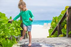 Little cute girl washes out the sand from her feet Stock Images