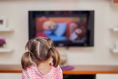 Little cute girl watching television with attention. Little cute girl watching tv at living room stock images