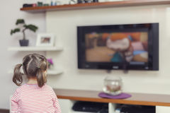 Little cute girl watching television Royalty Free Stock Photography
