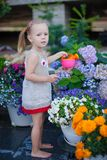 Little cute girl watering flowers with a Stock Photography