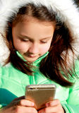 Little cute girl in whit fury hood with a cell phone Royalty Free Stock Images