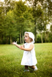 Little cute girl in white dress runs in summer park Royalty Free Stock Photos
