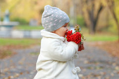 Little cute girl in white eats red rowanberry Stock Image