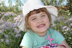 Little cute girl in white hat smiles near flowers Royalty Free Stock Image