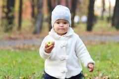 Little cute girl in white holds apple Stock Images
