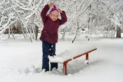 Little girl in winter outdoors. Little cute girl in winter outdoors. She throws snow up. Girl rejoices and fools stock image
