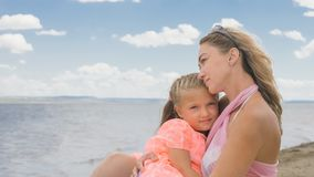 Little cute girl and young mother at beach. Little cute girl baby and young mother at beach. Mom sits on the shore, and her daughter is coming from behind. The Royalty Free Stock Photo