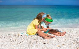 Little cute girls with big map on tropical beach Royalty Free Stock Photo