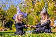 Little cute girls casting a spell on Halloween in Stock Photos