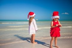 Little cute girls in Christmas hats on the exotic Royalty Free Stock Images