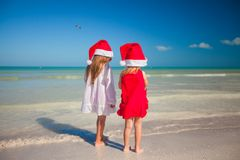 Little cute girls in Christmas hats on the exotic Stock Image