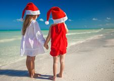 Little cute girls in Christmas hats on the exotic Royalty Free Stock Photo