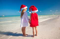 Little cute girls in Christmas hats on the exotic Royalty Free Stock Photos