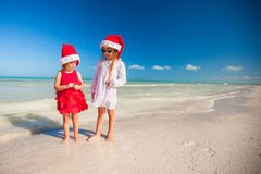 Little cute girls in Christmas hats on the exotic Stock Photos