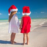 Little cute girls in Christmas hats on the exotic Stock Photography