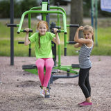Little cute girls doing exercises at public sports equipment. Sport. Royalty Free Stock Photos